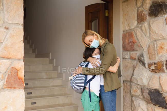 Kaukasische Frau und ihre Tochter betreten das Haus, tragen Mundschutz, stehen neben der Tür und umarmen sich. Soziale Distanzierung während Covid 19 Coronavirus Quarantäne Lockdown. — Stockfoto