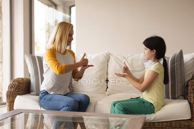 Femme caucasienne et sa fille passent du temps à la maison ensemble, portant des masques faciaux, ayant une conversation en langage gestuel. Distance sociale pendant le confinement en quarantaine du coronavirus Covid 19. — Photo de stock