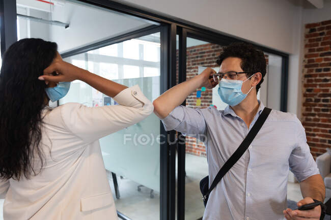 Mixed race woman and Caucasian man working in a casual office, wearing face masks and touching each others elbows. Social distancing in the workplace during Coronavirus Covid 19 pandemic. — Stock Photo