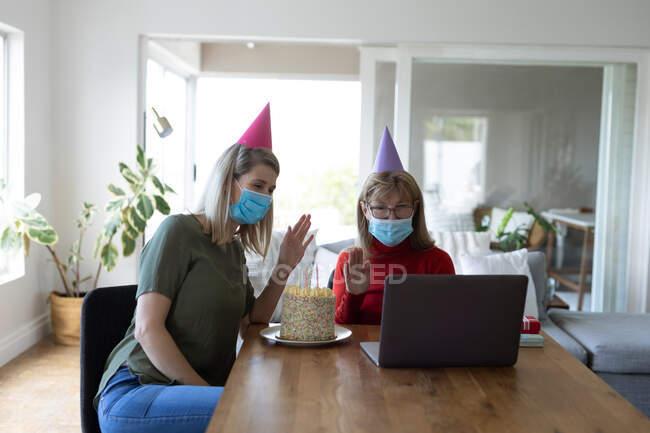 Eine ältere Frau aus dem Kaukasus verbringt ihre Zeit zu Hause mit ihrer erwachsenen Tochter, die im Wohnzimmer mit einer Geburtstagstorte sitzt und einen Laptop benutzt. Soziale Distanzierung während Covid 19 Coronavirus Quarantäne. — Stockfoto