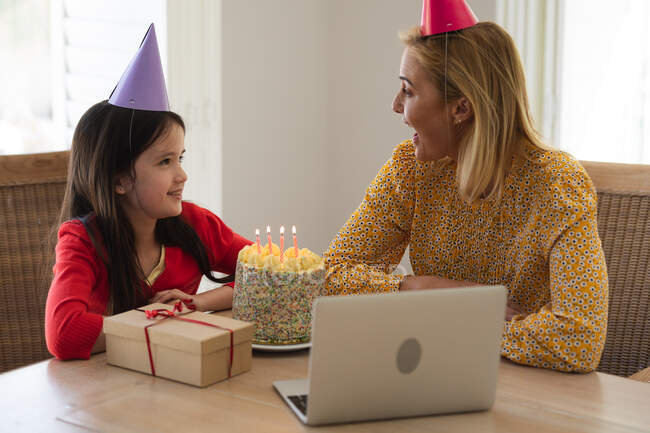 Caucasian woman and her daughter spending time at home together, celebrating birthday, using a laptop computer, making a video call. Social distancing during Covid 19 Coronavirus quarantine lockdown. — Stock Photo