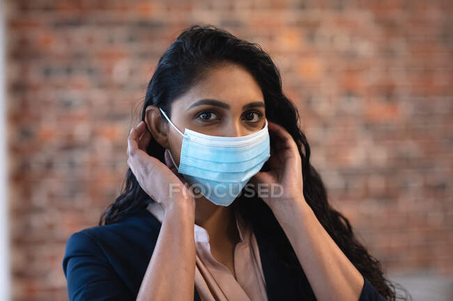 Portrait of mixed race woman working in a casual office, wearing face mask and looking at camera. Social distancing in the workplace during Coronavirus Covid 19 pandemic. — Stock Photo