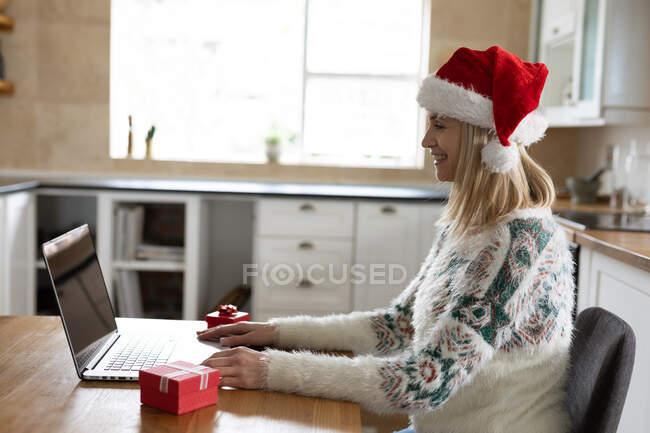 Femme caucasienne passant du temps à la maison, assis dans la cuisine à Noël portant le chapeau de Père Noël, en utilisant un ordinateur portable avec des cadeaux sur la table. Distance sociale pendant la quarantaine du coronavirus Covid 19. — Photo de stock