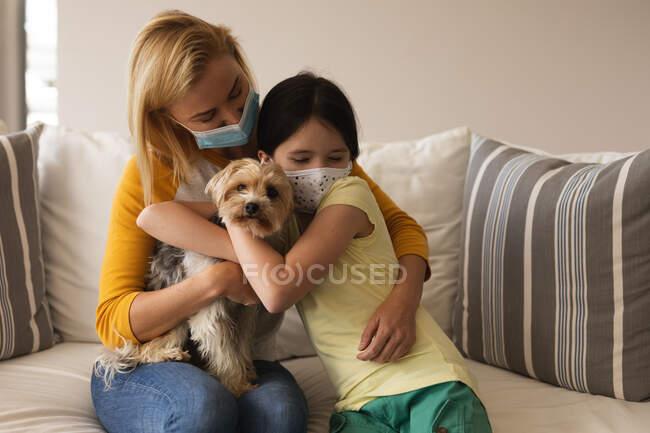 Femme caucasienne et sa fille passent du temps à la maison ensemble, portant des masques faciaux, embrassant leur chien. Distance sociale pendant le confinement en quarantaine du coronavirus Covid 19. — Photo de stock