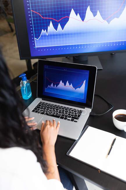 Donna razza mista che lavora in un ufficio informale, utilizzando il suo computer portatile e guardando i grafici. Distanze sociali sul luogo di lavoro durante la pandemia di Coronavirus Covid 19. — Foto stock
