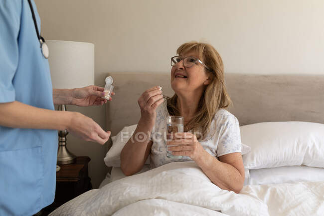 Senior Caucasian woman at home visited by Caucasian female nurse, taking medical pills. Medical care at home during Covid 19 Coronavirus quarantine. — Stock Photo