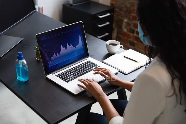Змішана раса жінка працює в повсякденному офісі, одягнена в маску обличчя і за допомогою ноутбука. Суспільна дистанція на робочому місці під час Коронавірусу Ковід 19 пандемії. — стокове фото