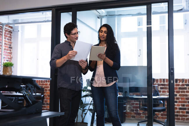 Mixed race woman and Caucasian man working in a casual office, using tablet and discussing their work. Creative business professionals working in a busy modern office. — Stock Photo