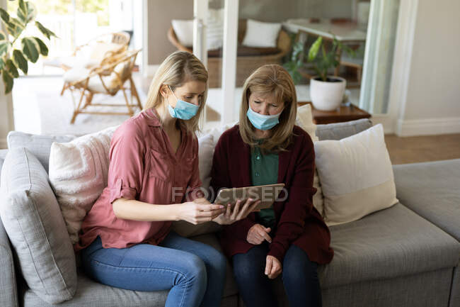 Senior Caucasian woman spending time at home with her adult daughter, sitting on couch, wearing face masks and using tablet computer. Social distancing during Covid 19 Coronavirus quarantine. — Stock Photo