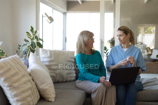 Senior Caucasian woman at home visited by Caucasian female nurse, sitting on a couch and using laptop. Medical care at home during Covid 19 Coronavirus quarantine. — Stock Photo