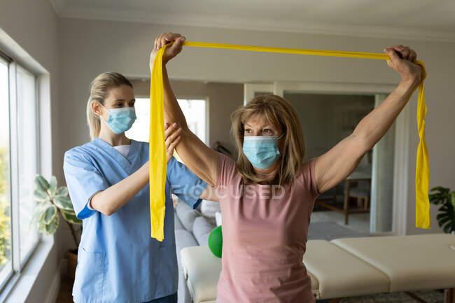 Mulher branca sênior em casa visitada por enfermeira caucasiana, estendendo os braços usando banda de exercício, usando máscaras faciais. Cuidados médicos em casa durante a quarentena do Coronavirus Covid 19. — Fotografia de Stock