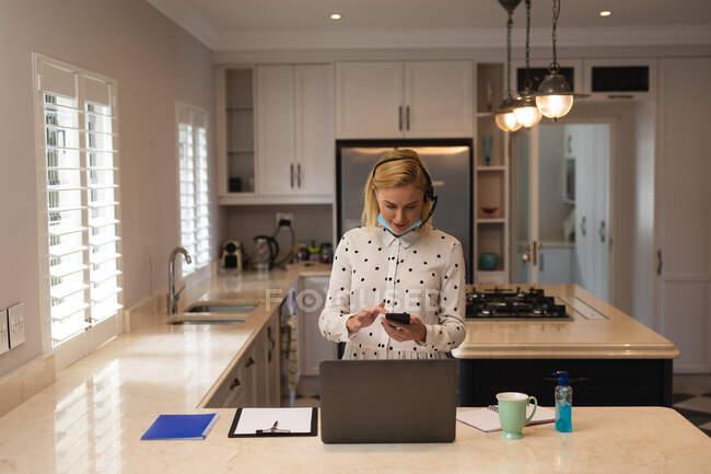 Кавказька жінка, що працює вдома, носить маску обличчя, користується смартфоном і ноутбуком. Соціальна дистанція в Ковиді 19 Коронавірус карантин. — стокове фото
