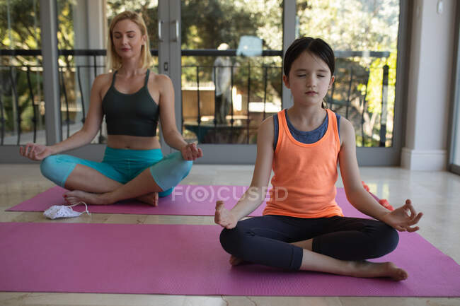 Caucasian woman and her daughter spending time at home together, doing yoga, meditating. Social distancing during Covid 19 Coronavirus quarantine lockdown. — Stock Photo