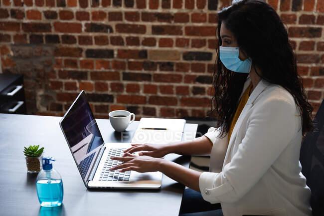 Mulher de raça mista trabalhando em um escritório casual, vestindo máscara facial e usando laptop. Distanciamento social no local de trabalho durante a pandemia do Coronavirus Covid 19. — Fotografia de Stock