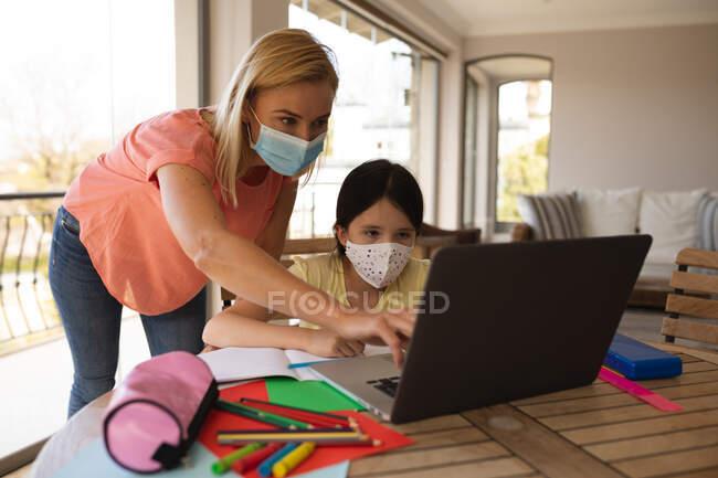 Femme caucasienne et sa fille passent du temps à la maison, portant des masques faciaux, utilisant un ordinateur portable pendant la leçon d'école en ligne. Distance sociale pendant le confinement en quarantaine du coronavirus Covid 19. — Photo de stock