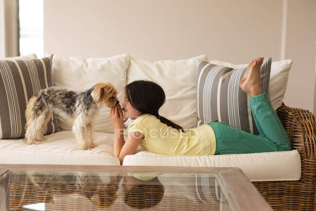 Caucasian girl spending time at home, wearing face mask, playing with her dog. Social distancing during Covid 19 Coronavirus quarantine lockdown. — Stock Photo