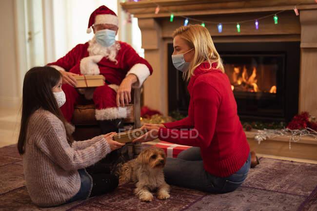 Старший кавказький чоловік, його доросла дочка і онука, одягнені як батько Різдва, одягнені в маску обличчя, даруючи подарунки. Соціальна дистанція в Ковиді 19 Коронавірус карантин. — стокове фото