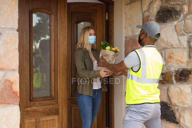 Caucasian woman spending time at home, wearing face mask, receiving a package from delivery man. Social distancing during Covid 19 Coronavirus quarantine lockdown. — Stock Photo