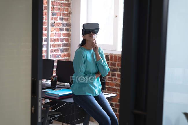 Змішана расова жінка працює в повсякденному офісі, одягнувши вр-гардероб, дивлячись на віртуальний екран. Суспільна дистанція на робочому місці під час Коронавірусу Ковід 19 пандемії. — стокове фото