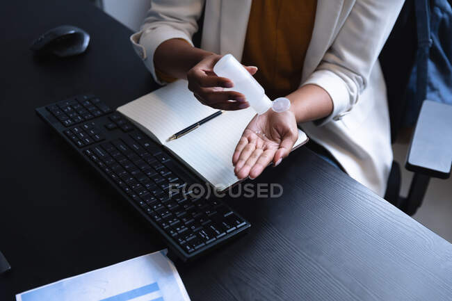 Закрой женщину, работающую в какой-нибудь офисе, за допомогою сканизатора. Суспільна дистанція на робочому місці під час Коронавірусу Ковід 19 пандемії. — стокове фото