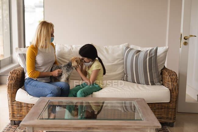 Kaukasische Frau und ihre Tochter verbringen Zeit zu Hause zusammen, tragen Gesichtsmasken, spielen mit ihrem Hund. Soziale Distanzierung während Covid 19 Coronavirus Quarantäne Lockdown. — Stockfoto