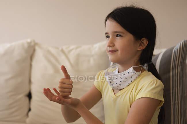 Kaukasisches Mädchen, das Zeit zu Hause verbringt, Gesichtsmaske trägt und Gebärdensprache benutzt. Soziale Distanzierung während Covid 19 Coronavirus Quarantäne Lockdown. — Stockfoto