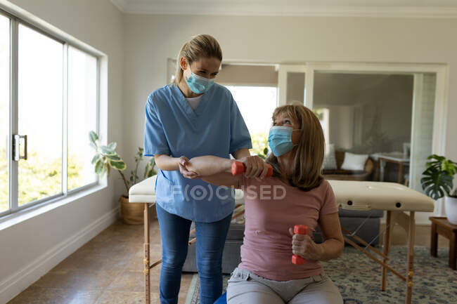 Senior Caucasian woman at home visited by Caucasian female nurse, stretching her arm, wearing face masks. Medical care at home during Covid 19 Coronavirus quarantine. — Stock Photo