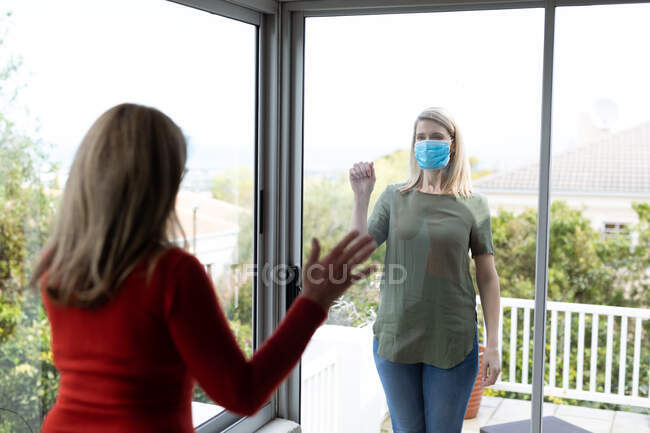 Senior Caucasian woman and her adult daughter at home, wearing face masks and greeting each other through window. Social distancing, health and hygiene during Covid 19 Coronavirus pandemic. — Stock Photo