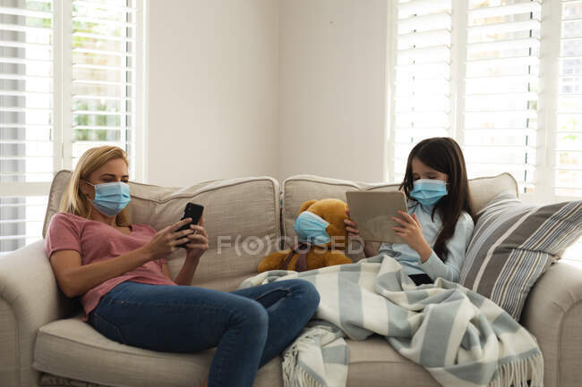 Caucasian woman and her daughter spending time at home together, wearing face masks, sitting on a sofa, using smartphone and tablet. Social distancing during Covid 19 Coronavirus quarantine lockdown. — Stock Photo