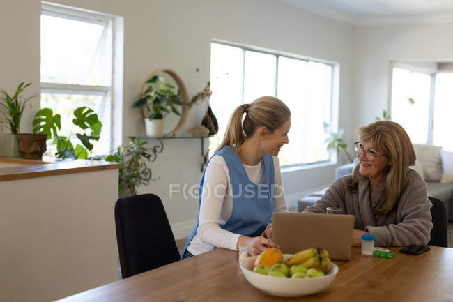 Senior Caucasian woman at home visited by Caucasian female nurse, sitting by table using laptop computer. Medical care at home during Covid 19 Coronavirus quarantine. — Stock Photo