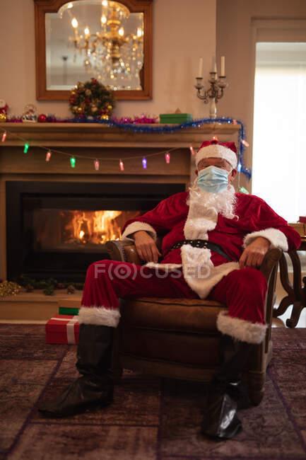 Старша кавказька людина вдома, одягнена як Отець Різдво, одягнена в маску обличчя, сидячи на стільці біля каміна. Соціальна дистанція в Ковиді 19 Коронавірус карантин. — стокове фото