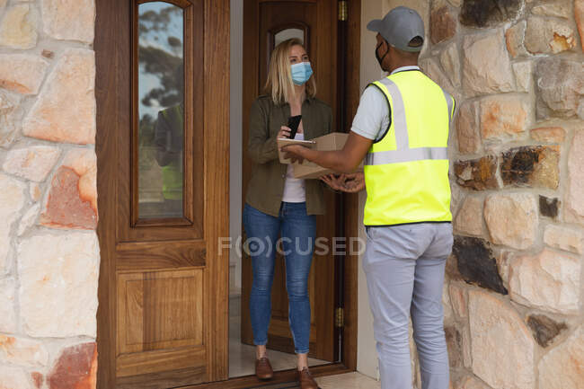 Caucasian woman spending time at home, wearing face mask, receiving a package from delivery man and paying by smartphone. Social distancing during Covid 19 Coronavirus quarantine lockdown. — Stock Photo