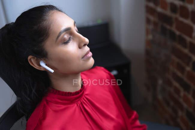 Mulher de raça mista trabalhando em um escritório casual, usando fones de ouvido e ouvindo música. Distanciamento social no local de trabalho durante a pandemia do Coronavirus Covid 19. — Fotografia de Stock