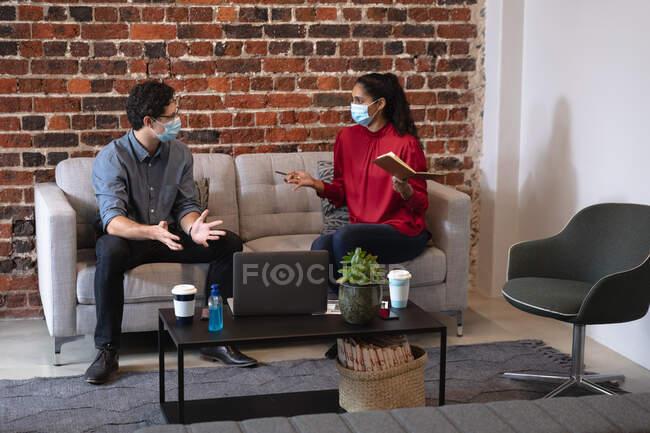 Donna di razza mista e uomo caucasico che lavorano in un ufficio casual, indossano maschere facciali, si siedono su un divano e parlano. Distanze sociali sul luogo di lavoro durante la pandemia di Coronavirus Covid 19. — Foto stock