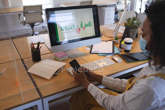 Donna di razza mista seduta alla scrivania in un ufficio moderno con una maschera facciale, utilizzando uno smartphone e un computer. Salute e igiene sul luogo di lavoro durante la pandemia di Coronavirus Covid 19. — Foto stock
