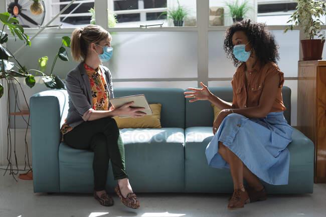 Razza mista e creativi aziendali caucasici che indossano maschere facciali e si allontanano sul divano, parlando e utilizzando tablet in ufficio. Salute e igiene sul luogo di lavoro durante la pandemia di Coronavirus Covid 19. — Foto stock