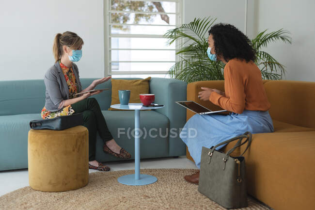Mixed race and Caucasian female creatives wearing face masks and social distancing at a work meeting. Health and hygiene in the workplace during Coronavirus Covid 19 pandemic. — Stock Photo