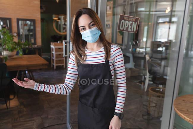 Peluquería femenina caucásica trabajando en peluquería con mascarilla, dando la bienvenida a los clientes en la entrada. Salud e higiene en el lugar de trabajo durante la pandemia de Coronavirus Covid 19. - foto de stock
