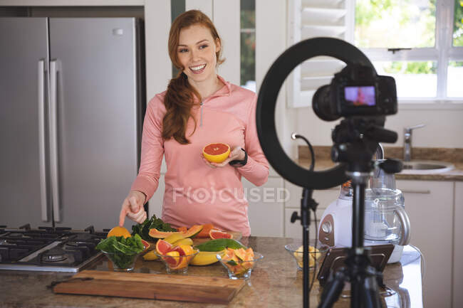 Caucasian woman spending time at home, chopping fruit in the kitchen, recording it with a camera. Social distancing during Covid 19 Coronavirus quarantine lockdown. — Stock Photo