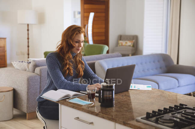 Caucasian woman spending time at home, in the kitchen, working from home, using her laptop. Social distancing during Covid 19 Coronavirus quarantine lockdown. — Stock Photo