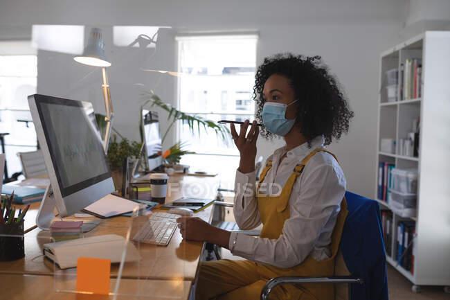 Donna mista che lavora alla scrivania in un ufficio moderno indossando una maschera facciale e parlando su uno smartphone. Salute e igiene sul luogo di lavoro durante la pandemia di Coronavirus Covid 19. — Foto stock