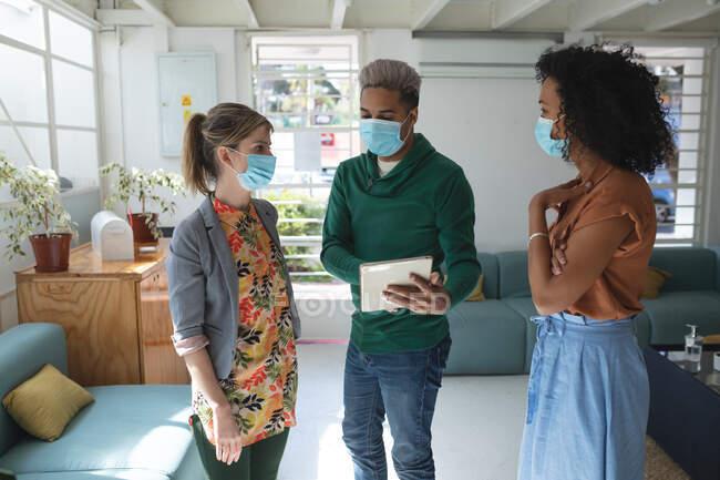 Multi gruppo etnico di uomini e donne creativi d'affari che indossano maschere facciali in ufficio brainstorming utilizzando tablet. Salute e igiene sul luogo di lavoro durante la pandemia di Coronavirus Covid 19. — Foto stock