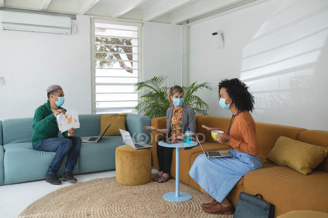 Multi ethnic group of male and female creatives wearing face masks and social distancing at a work meeting. Health and hygiene in the workplace during Coronavirus Covid 19 pandemic. — Stock Photo