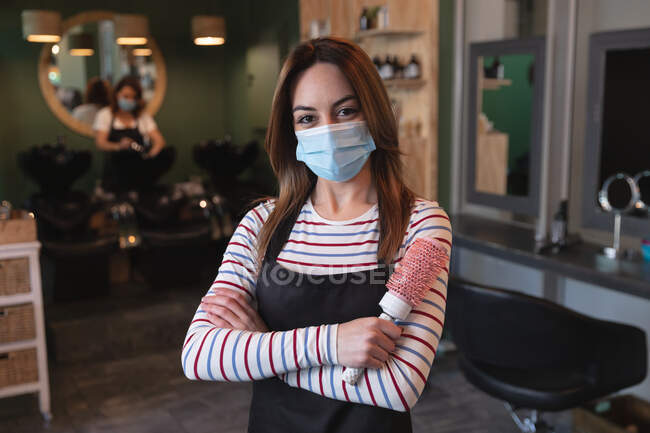 Portrait of a Caucasian female hairdresser working in hair salon wearing face mask, posing for a photo, holding a hairbrush. Health and hygiene in workplace during Coronavirus Covid 19 pandemic. — Stock Photo