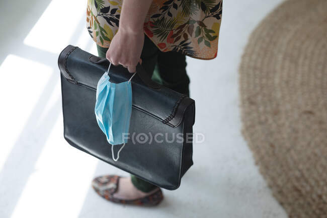 Mid section of female business creative standing in office foyer holding briefcase and face mask. Health and hygiene in workplace during Coronavirus Covid 19 pandemic. — Stock Photo