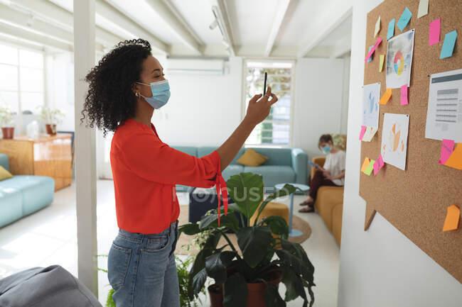 Frauen mit gemischter Rasse stehen kreativ in einem Büro und tragen Gesichtsmasken, die ein Foto von der Anzeigetafel machen. Gesundheit und Hygiene am Arbeitsplatz während der Coronavirus Covid 19 Pandemie. — Stockfoto