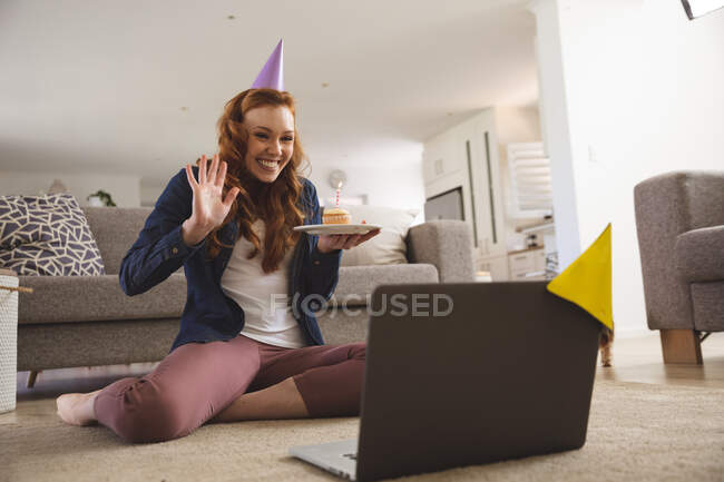Caucasian woman spending time at home, in living room, smiling, celebrating, holding a cupcake with a candle. Social distancing during Covid 19 Coronavirus quarantine lockdown. — Stock Photo