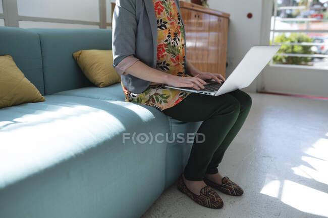 Donna caucasica business creativo seduto sul divano in un ufficio utilizzando il suo computer portatile. Salute e igiene sul luogo di lavoro durante la pandemia di Coronavirus Covid 19. — Foto stock
