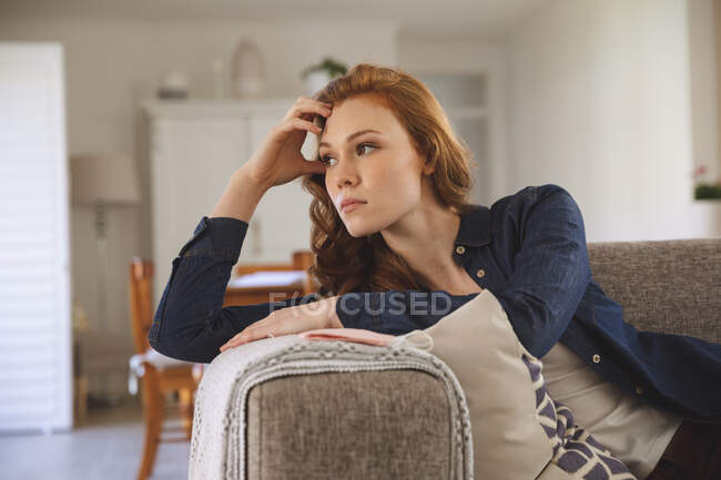 Caucasian woman spending time at home, in living room, lying on the couch, looking sad. Social distancing during Covid 19 Coronavirus quarantine lockdown. — Stock Photo