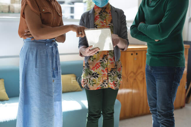 Multi ethnic group of male and female business creatives wearing face masks in office brainstorming using tablet. Health and hygiene in the workplace during Coronavirus Covid 19 pandemic. — Stock Photo